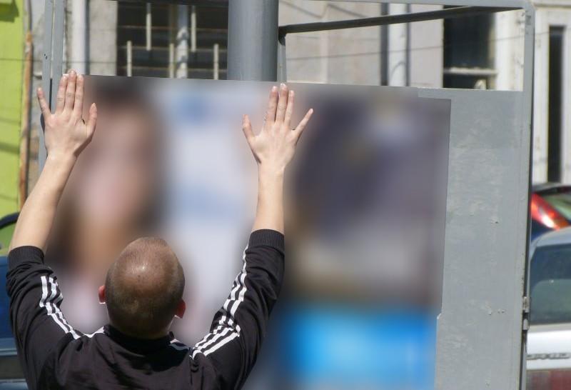 Мъж, нает за разлепване на предизборни плакати